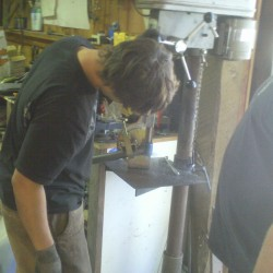 Paul using the drill press for notching cage tubing.