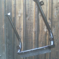 This is our front skid pan frame hanging upside down after being painted. But at least it's naked and you can see the basics of it. The clamps attach to the beam, the tabs on the bars attach to the underside of the bumper, and the angle iron attaches to the front of the bumper. Installed, the five front bolts are at the middle of the bumper. The tabs in the rear next to the beam clamps is where the skid pan attaches underneath. Remember, use Grade 8 bolts.